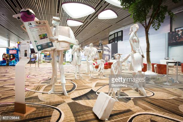 A sculpture piece titled 'Travelling Family' by Kurt Metzier stands in the departure transit area during a media preview of the new Terminal 4 at...
