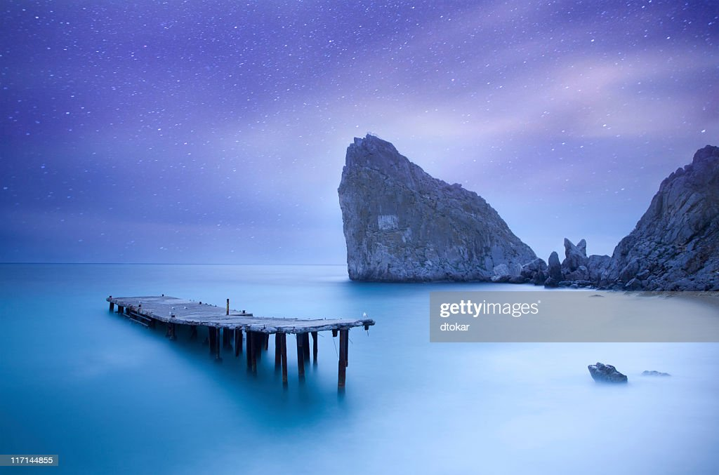 Sea at night under milky way stars with pier : Stock Photo
