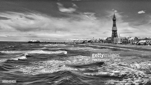 Sea By Blackpool Tower Against Cloudy Sky