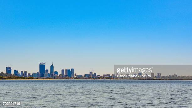 Sea By Cityscape Against Clear Sky