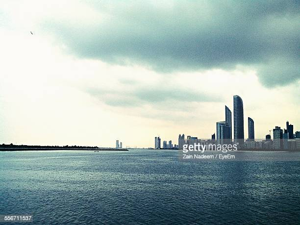 Sea By Cityscape Against Cloudy Sky