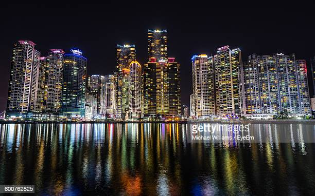 Sea By Illuminated Modern Buildings Against Clear Sky At Night