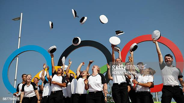 Sea cadets from the training ship 'The Danmark' throw their hats in the air as they pose for a photograph in front of the Olympic rings at the...