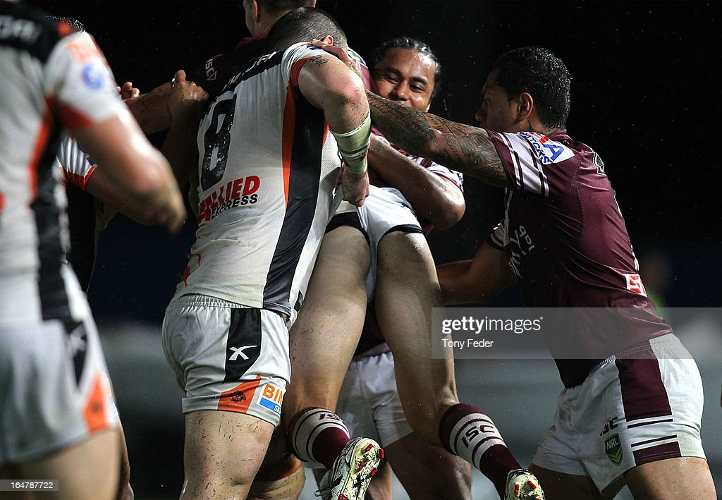 A Sea Eagles player has his shorts pulled by Aaron Woods of the Wests Tigers during the round four NRL match between the Manly Sea Eagles and the Wests Tigers at Bluetongue Stadium on March 28, 2013 in Gosford, Australia.
