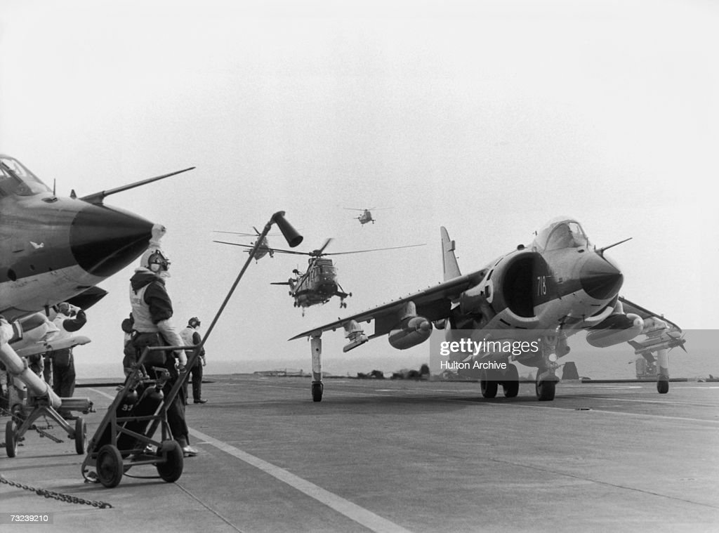 A Sea Harrier jump jet on the flight deck of HMS Hermes heading to the Falklands after the Argentinian invasion of the islands April 1982 A Sea King...
