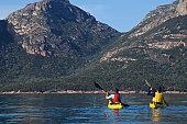 Sea kayakers on a calm morning in Coles Bay, Freycinet National Park, Tasmania, Australia.