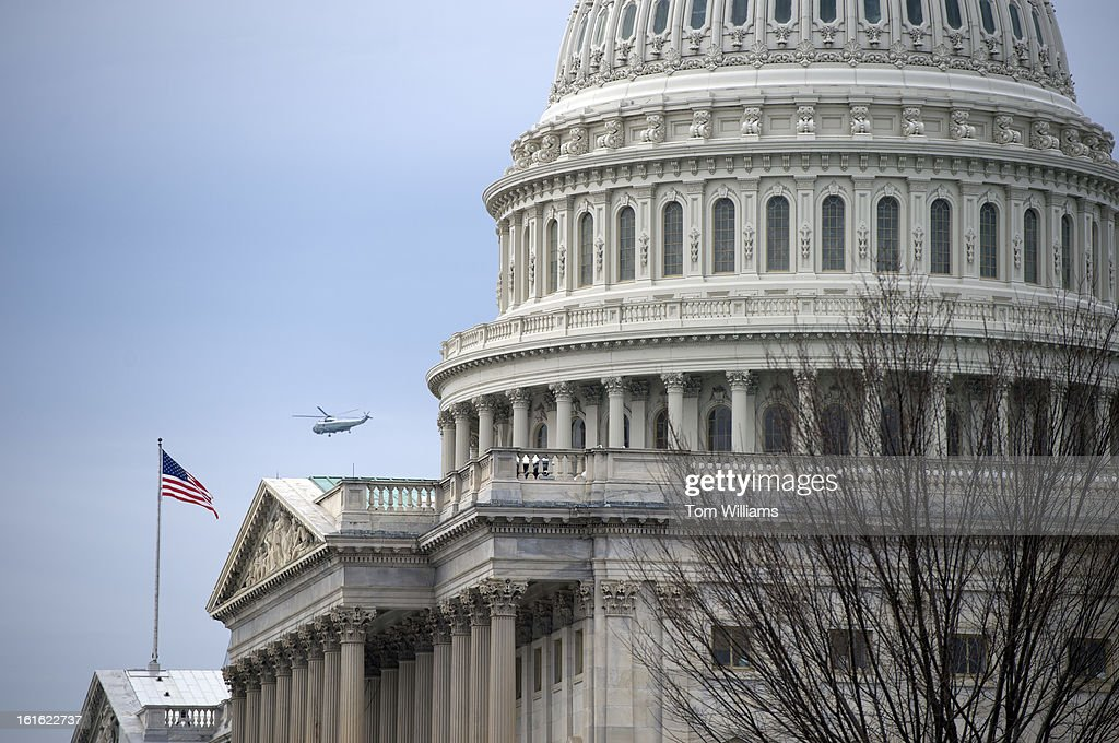 Sea King helicopter, the kind that carries the President of the United States, flies past the Capitol Building.