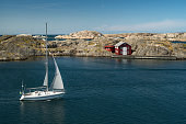 Sea landscape with yachts and rocky coastline on the South of Sweden. Southern coastline of Sweden with view at sailing-ships and rocky islands. Red fishing houses on the shore.