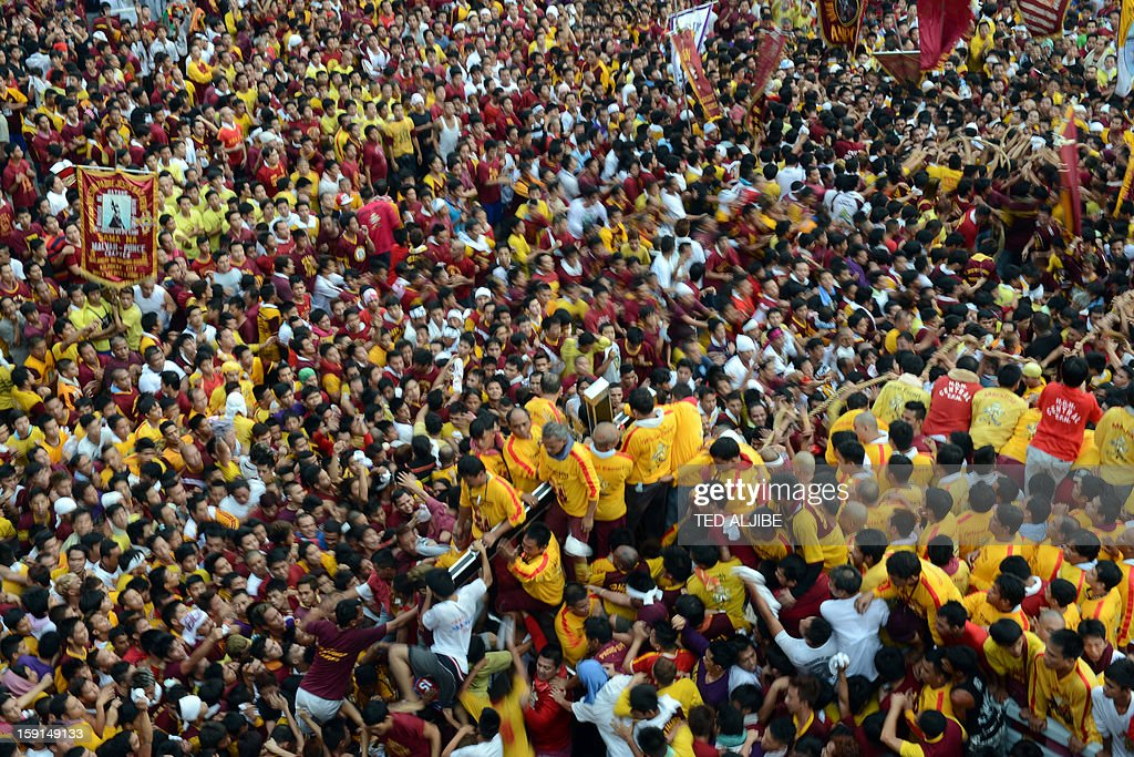 A sea of Catholic devotees jostle for position as they try to reach a life-size statue (C) of the Black Nazarene during the annual procession in honor of the centuries-old icon of Jesus Christ in Manila on January 9, 2013. Masses of Catholic devotees swept through the Philippine capital on January 9, in a spectacular outpouring of passion for a centuries-old icon of Jesus Christ that many believe can perform miracles.