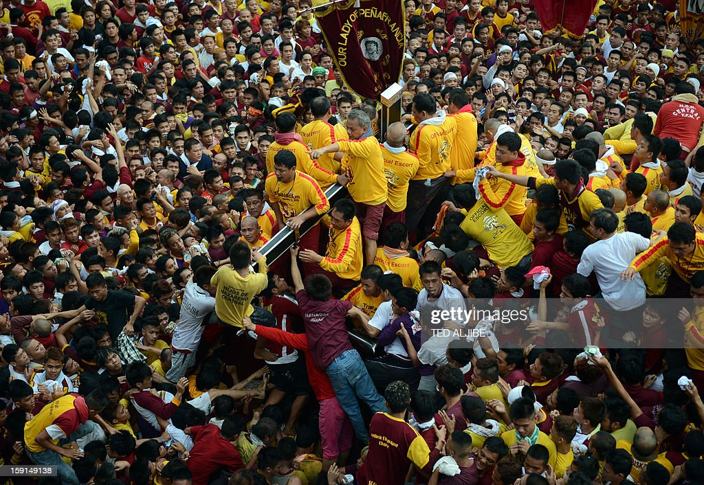A sea of Catholic devotees jostle for position as they try to reach the life-size statue of the Black Nazarene during the annual procession in honor of the centuries-old icon of Jesus Christ in Manila on January 9, 2013. Masses of Catholic devotees swept through the Philippine capital on January 9, in a spectacular outpouring of passion for a centuries-old icon of Jesus Christ that many believe can perform miracles.