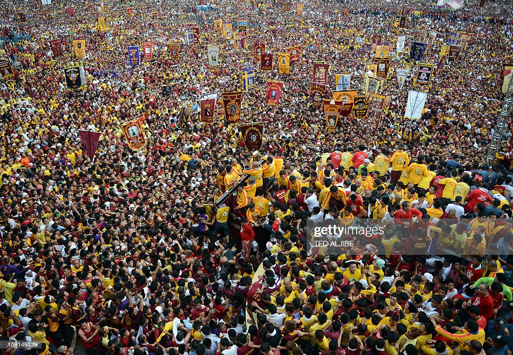 A sea of Catholic devotees jostle for position as they try to touch the life-size statue of the Black Nazarene during the annual procession in honor of the centuries-old icon of Jesus Christ in Manila on January 9, 2013. Masses of Catholic devotees swept through the Philippine capital on January 9, in a spectacular outpouring of passion for a centuries-old icon of Jesus Christ that many believe can perform miracles. AFP PHOTO/TED ALJIBE