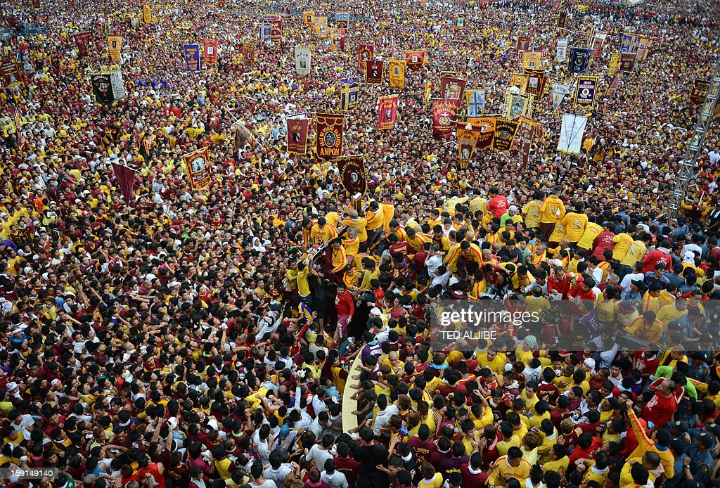 A sea of Catholic devotees jostle for position as they try to touch the life-size statue of the Black Nazarene during the annual procession in honor of the centuries-old icon of Jesus Christ in Manila on January 9, 2013. Masses of Catholic devotees swept through the Philippine capital on January 9, in a spectacular outpouring of passion for a centuries-old icon of Jesus Christ that many believe can perform miracles.