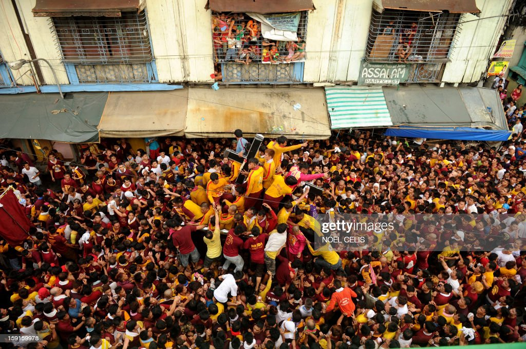 A sea of Catholic devotees jostle for position as they try to touch the life-size statue of the Black Nazarene during the annual procession in honor of the centuries-old icon of Jesus Christ in Manila on January 9, 2013. Masses of Catholic devotees swept through the Philippine capital on January 9, in a spectacular outpouring of passion for a centuries-old icon of Jesus Christ that many believe can perform miracles. AFP PHOTO/NOEL CELIS
