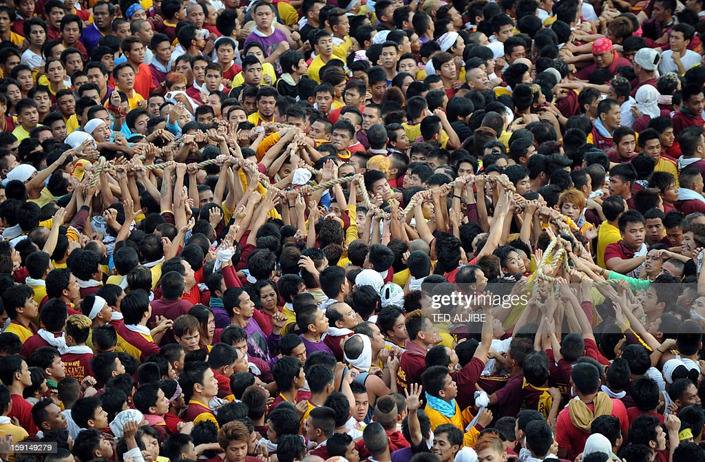 A sea of Catholic devotees touch the rope (C) used to pull the carriage carrying the life-size statue of the Black Nazarene (not pictured) during an annual procession in honor of the centuries-old icon of Jesus Christ in Manila on January 9, 2013. Masses of Catholic devotees swept through the Philippine capital on January 9, in a spectacular outpouring of passion for a centuries-old icon of Jesus Christ that many believe can perform miracles. AFP PHOTO/TED ALJIBE