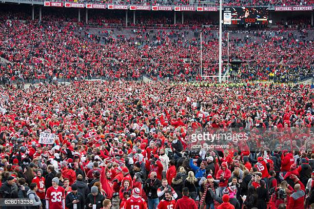 A sea of scarlet and grey consume the field following an NCAA football game between the Michigan Wolverines and the Ohio State Buckeyes on November...