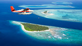 Sea plane flying above Maldives islands, concept of travel and vacation