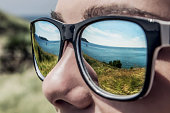 Tropical lanscape reflected in young man's sunglasses