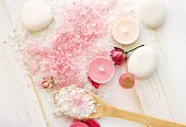 Natural Sea salt aromatherapy pink herbal relaxing products spa setting background, top view.