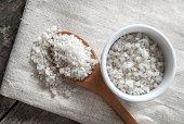 sea salt in wooden spoon on wooden background