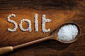 Sea salt on wooden spoon and the word salt written in grain