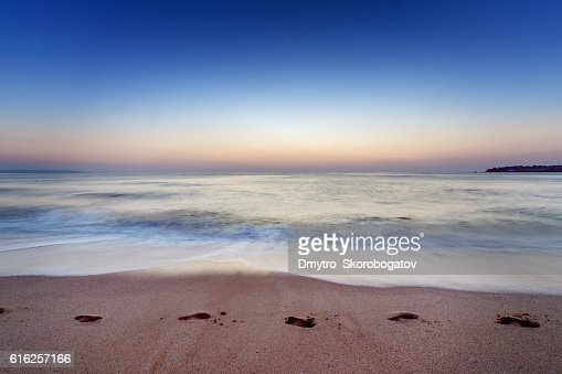 sea shore with a sandy beach with traces of feet : Foto de stock