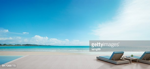 Sea view swimming pool beside terrace and beds in modern luxury beach house with blue sky background, Lounge chairs on wooden deck at vacation home or hotel : Stock Photo