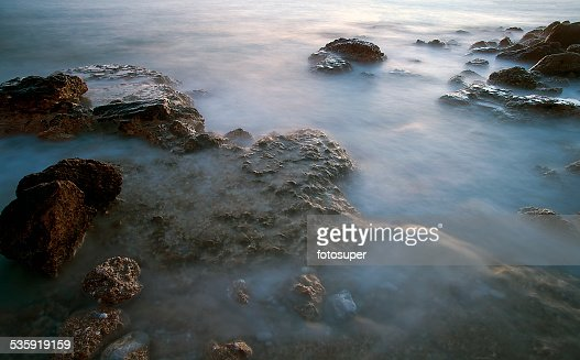 sea wave beach sand stones and long exposure : Stock Photo