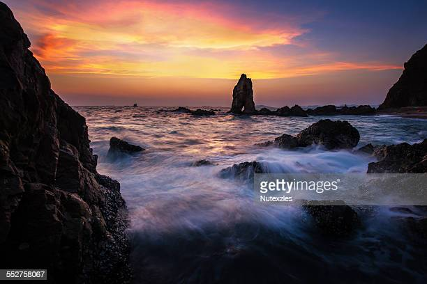 Sea wave hit the rock at sunset in Pattaya