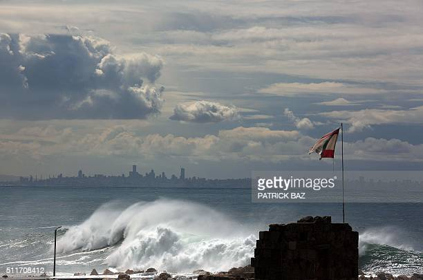 Sea waves hit the world oldest port of Byblos as the Lebanese capital Beirut appears in the background on February 22 2016 / AFP / PATRICK BAZ