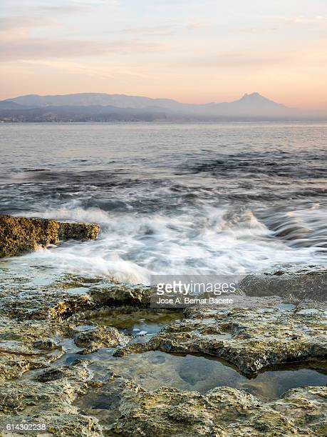 Sea waves moving over an area of rocks at sunrise