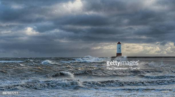 Sea Waves Rushing Towards Lighthouse Against Cloudy Sky
