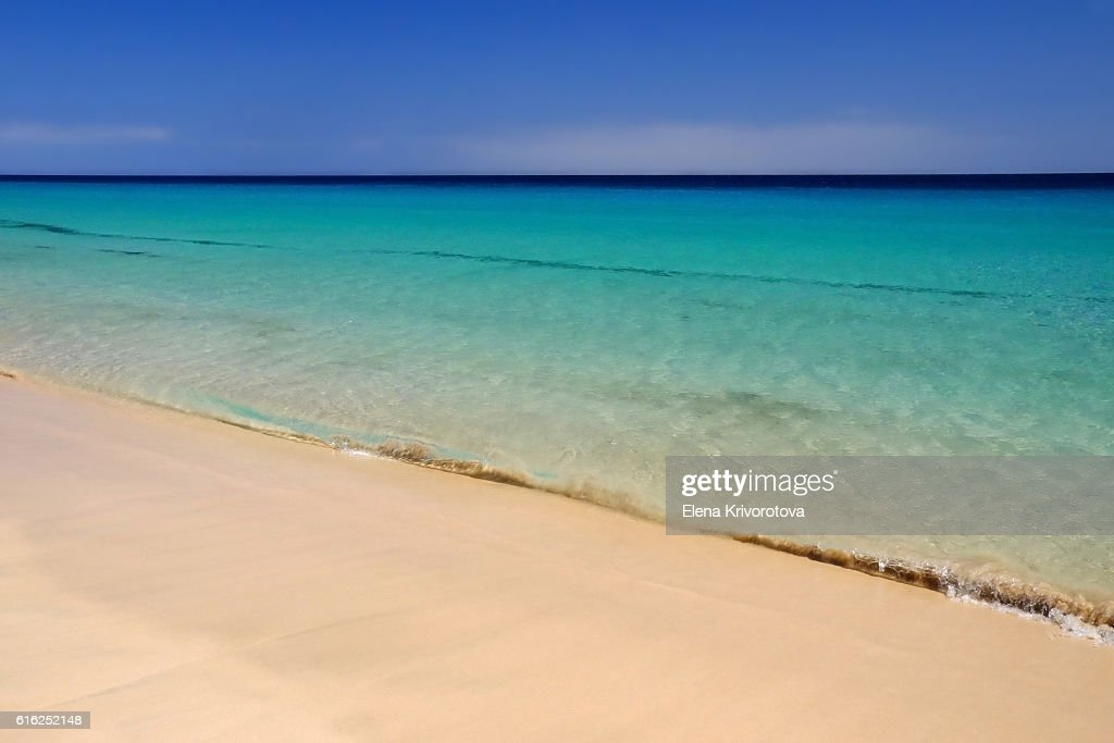 Sea with crystal water and golden sand on the beach. : Foto de stock