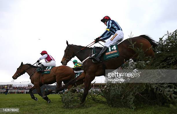 Seabass ridden by Katie Walsh clears the last fence alongside Sunnyhillboy ridden by Ritchie McLernon and Shakalakaboomboom ridden by Barry Geraghty...