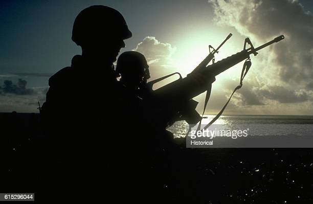 Seabees and Marines are silhouetted against the morning sky as they stand by to begin firing their M16A1 rifles Seabees from Naval Mobile...