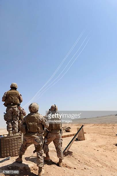 Seabees watch rockets fire overhead.