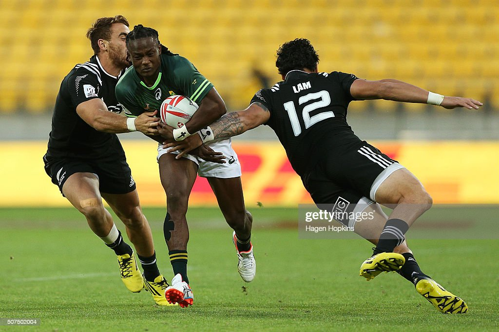 Seabelo Senatla of South Africa is tackled by Joe Webber and Ben Lam of New Zealand during the 2016 Wellington Sevens pool match between South Africa...