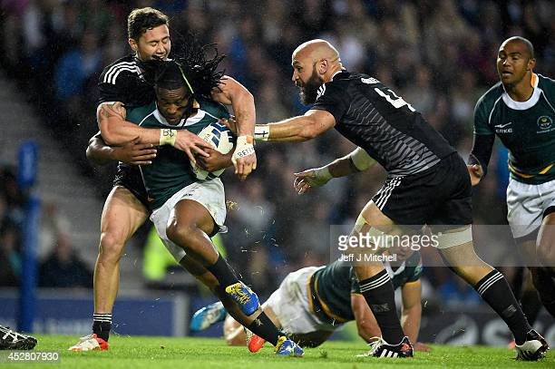 Seablo Sentala of South Africa is tackled by Gillies Kaka and D J Forbes of New Zealand during the gold medal rugby sevens match at Ibrox Stadium...
