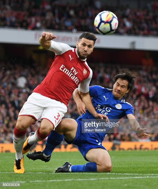 Sead Kolasinac of Arsenal is tackled by Shinji Okazaki of Leicester City during the Premier League match between Arsenal and Leicester City at the...