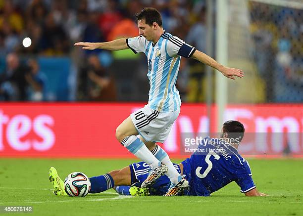 Sead Kolasinac of Bosnia and Herzegovina tackles Lionel Messi of Argentina during the 2014 FIFA World Cup Brazil Group F match between Argentina and...