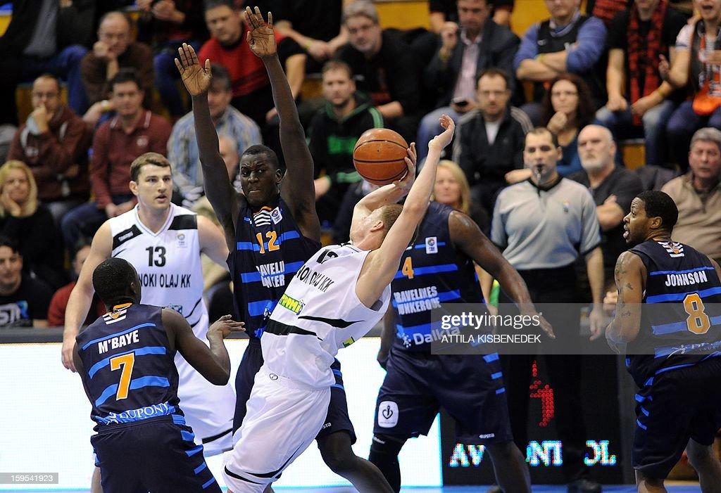 Sead Sehivic (C) of Hungarian KK Szolnoki Olaj is fouled by Juan Edwards (C-R) of French BCM Gravelines Dunkerque on January 15, 2015 during their FIBA EuroChallenge match. AFP PHOTO / ATTILA KISBENEDEK