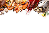 Border of different types of seafood including sea bream, mussel, crab, clams, salmon, shrimps, and prawns. Seafood is arranged at the upper border of the frame leaving a plenty copy space in the cent