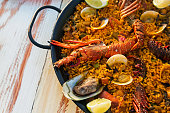 Seafood paella on the wooden table close-up