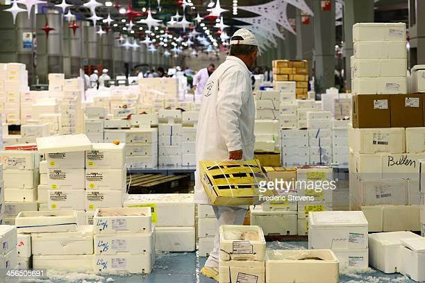 A seafood wholesaler prepares some of the catch at the Rungis market in seafood department on December 13 2013 in Rungis France Rungis is the world's...