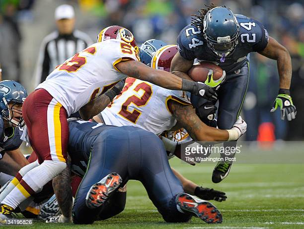 Seahawks running back Marshawn Lynch right is stopped at the line by Redskins inside linebacker Perry Riley left and Redskins defensive end Stephen...