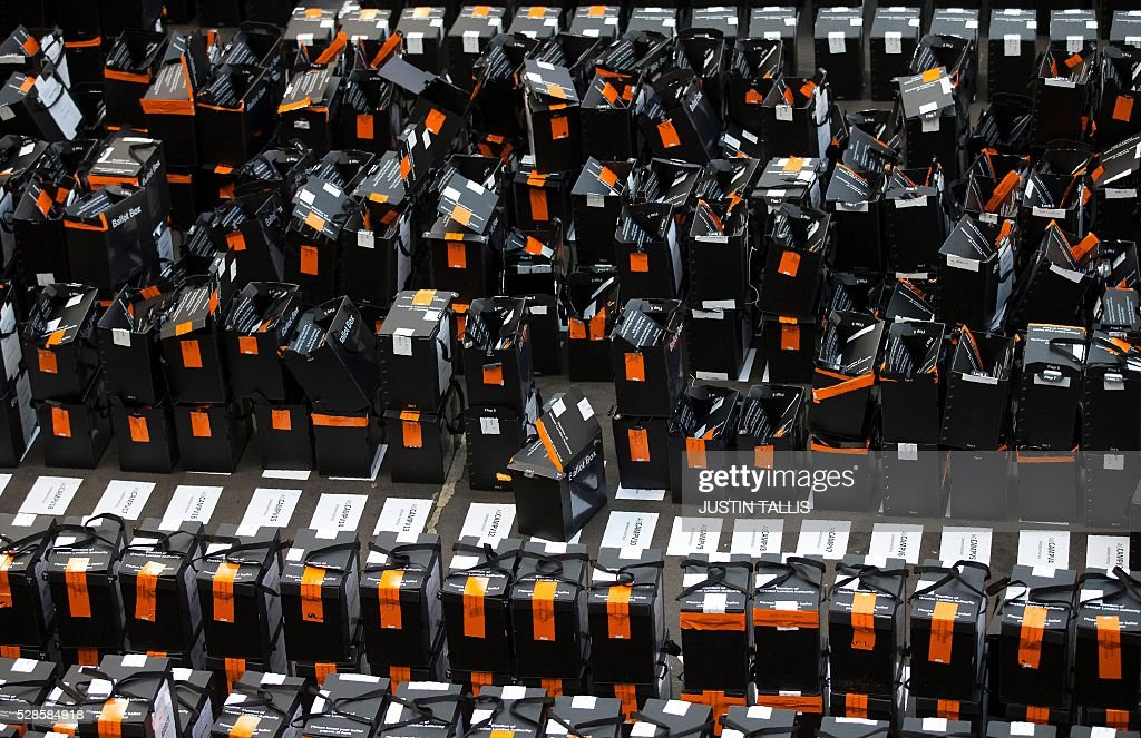 Sealed ballot boxes await processing as opened and emptied ones are pictured beyoned, at a count centre in north London on May 6, 2016. Early results Friday from British local and regional elections seen as a key test for opposition Labour leader Jeremy Corbyn showed strong gains for Scottish nationalists, as London looked set to elect its first Muslim mayor. London was on track to become the first EU capital with a Muslim mayor as voters went to the polls Thursday after a bitter campaign between Prime Minister David Cameron's Conservatives and the opposition Labour party. / AFP / JUSTIN
