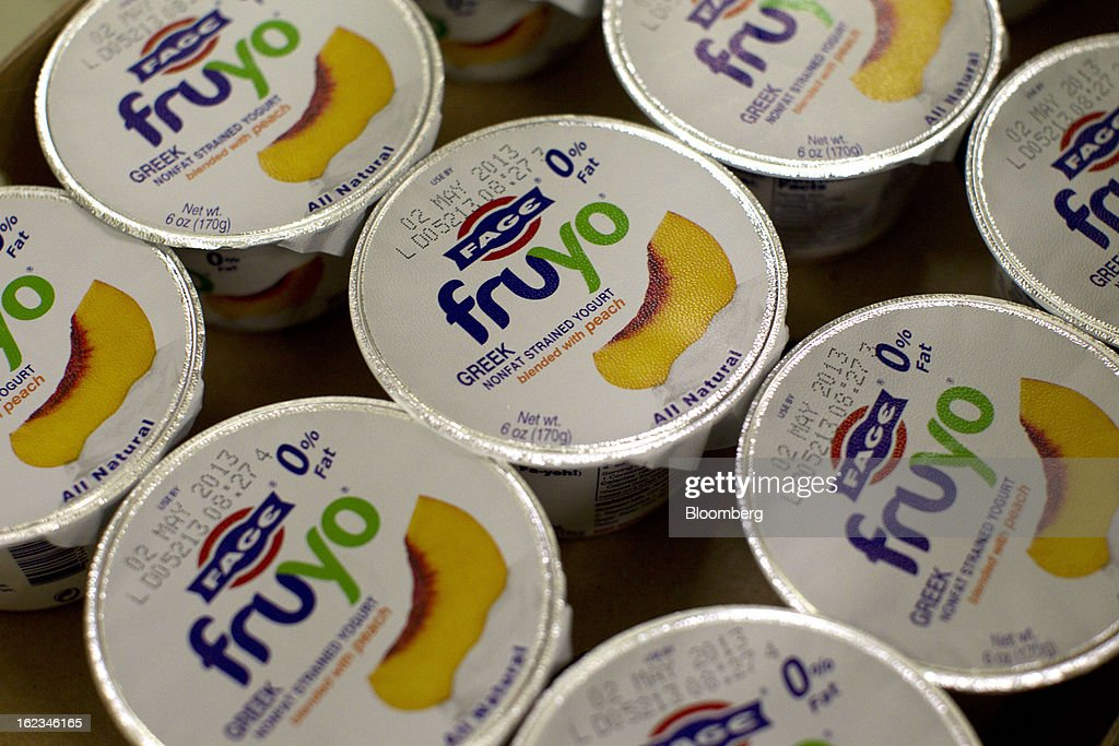Sealed cartons of Fruyo peach-blended Greek yoghurt pass stand in a shipping tray after manufacture at the Fage Dairy Industry SA plant in Athens, Greece, on Thursday, Feb. 21, 2013. An October restructuring that placed Fage International SA's Greek units in a subsidiary called Fage Dairy Industry SA coincided with Coca-Cola Hellenic Bottling SA's plan to flee the epicenter of Europe's debt crisis by moving its main stock listing to London from Athens. Photographer: Kostas Tsironis/Bloomberg via Getty Images
