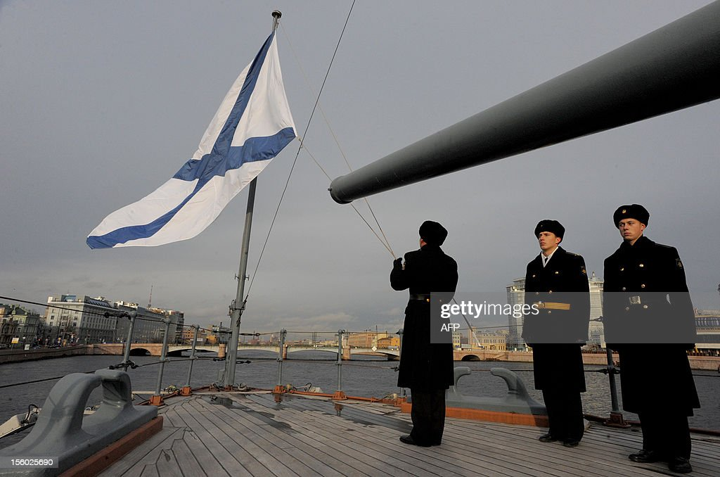 A seaman lowers the Russian navy flag to half mast as parf of a ceremony marking the anniversary of the end of the World War I aboard the legendary cruiser Aurora in St. Petersburg on November 11, 2012.