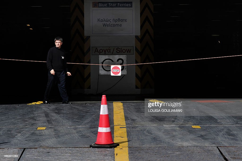 A seaman stands at the entrance to an anchored ferry at the port of Piraeus on April 3, 2013. Ferry services between the numerous Greek islands and the mainland was disrupted on April 3, as seamen launched a 24-hour strike protesting against reforms in their sector. The Panhellenic Seamens' Union (PNO) organised the strike to oppose a law that will allow the number of crew members aboard ships sailing under a Greek flag to be reduced.According to PNO, unemployment in the sector has hit more than 7,000 maritime workers, out of a total of 15,000 active workers.