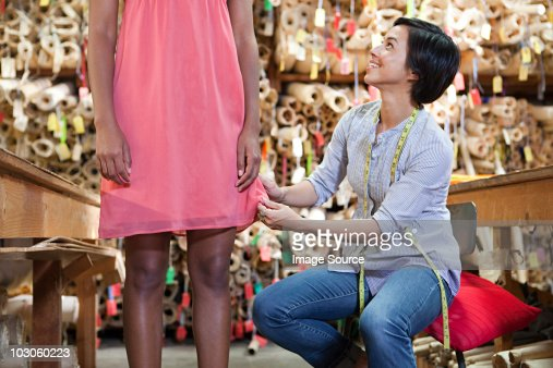 Seamstress adjusting dress on model