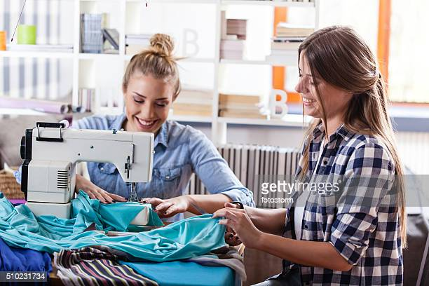 Seamstress and fashion designer sewing together